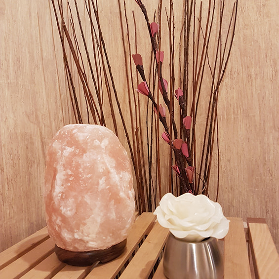Himalayan salt lamp, massage oil and decorative flowers, taken at the west edmonton clinic